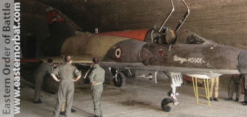 "French and Egyptian ground crews inspect Egyptian Air Force Mirage 5SDE ""9111"" in a shelter at an unknown Air Base before a mission."